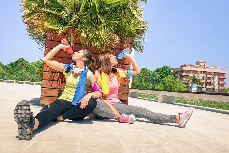 Φίλαθλες νέες γυναίκες που πίνουν τον ενεργητικό χυμό στην κατάρτιση τρεξίματος στοκ εικόνες