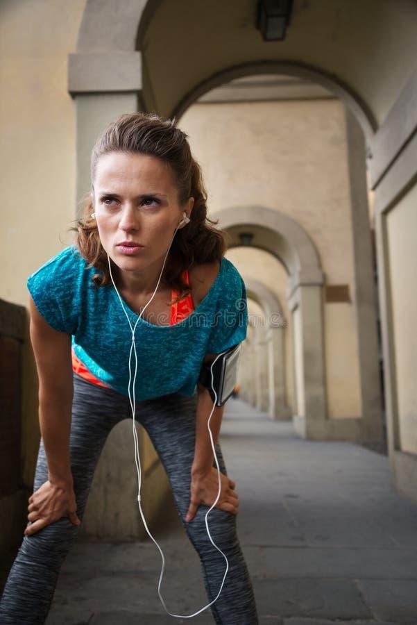 Φίλαθλη γυναίκα με τα ακουστικά που πιάνουν την αναπνοή μετά από στοκ εικόνες