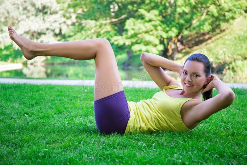 Φίλαθλη γυναίκα που κάνει τις ασκήσεις για τους κοιλιακούς μυς στο πάρκο στοκ εικόνα