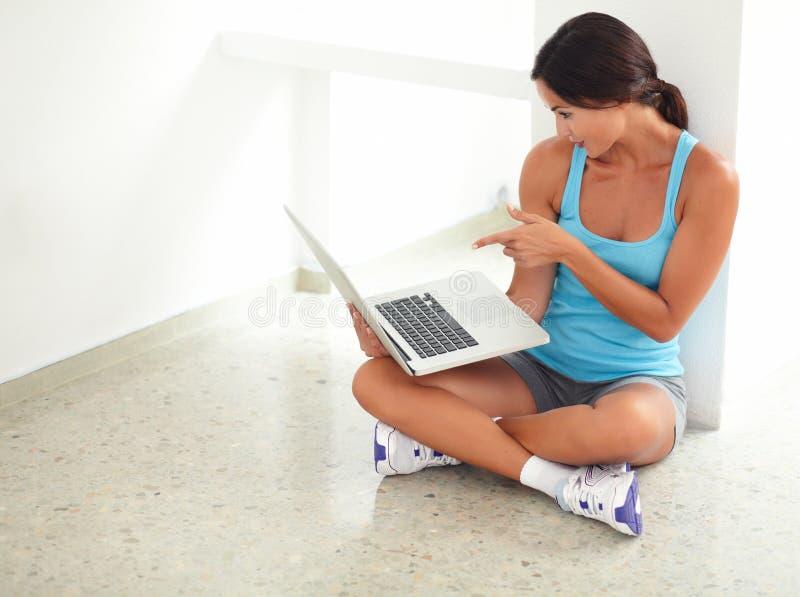 Φίλαθλη γυναίκα brunette που δείχνει στο lap-top της στοκ εικόνα με δικαίωμα ελεύθερης χρήσης