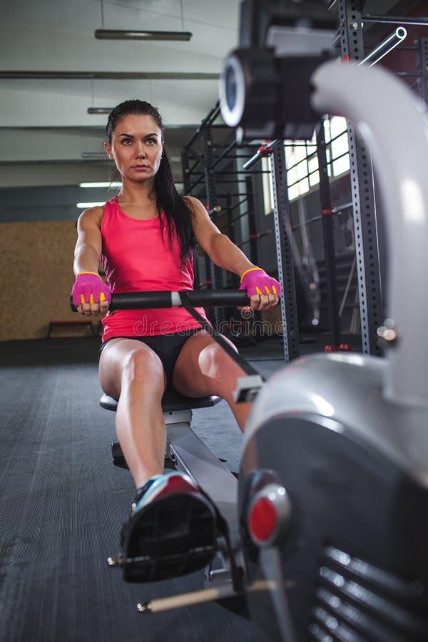 φίλαθλη γυναίκα workout στη μηχανή κωπηλασίας στη γυμναστική στοκ εικόνες