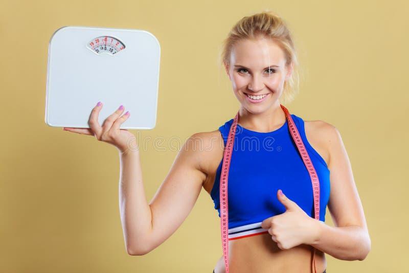 Φίλαθλη ευτυχής γυναίκα με την κλίμακα, απώλεια βάρους στοκ εικόνα
