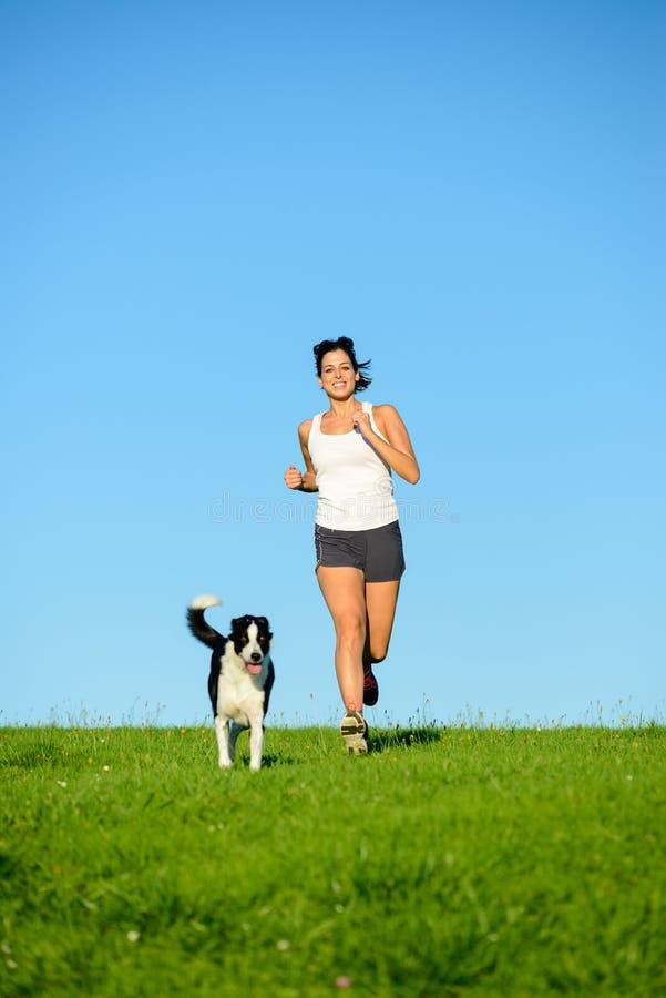 Φίλαθλη ευτυχής γυναίκα που τρέχει με το σκυλί στοκ εικόνες