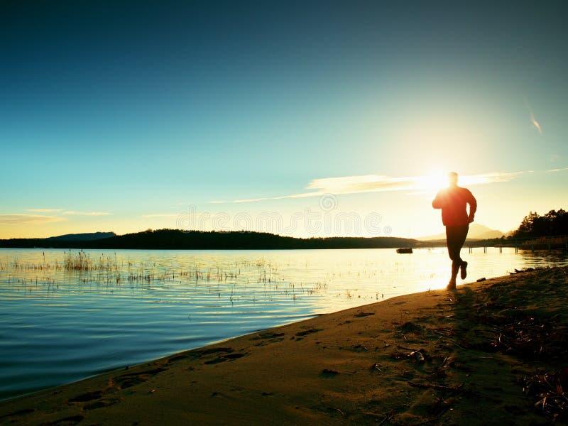Φίλαθλο άτομο που κάνει το πρωί Jogging στην παραλία θάλασσας στις φωτεινές σκιαγραφίες ανατολής στοκ εικόνα με δικαίωμα ελεύθερης χρήσης