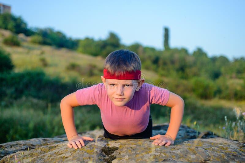 Φίλαθλο νέο αγόρι που κάνει την ώθηση επάνω πάνω από το λίθο στοκ φωτογραφίες με δικαίωμα ελεύθερης χρήσης