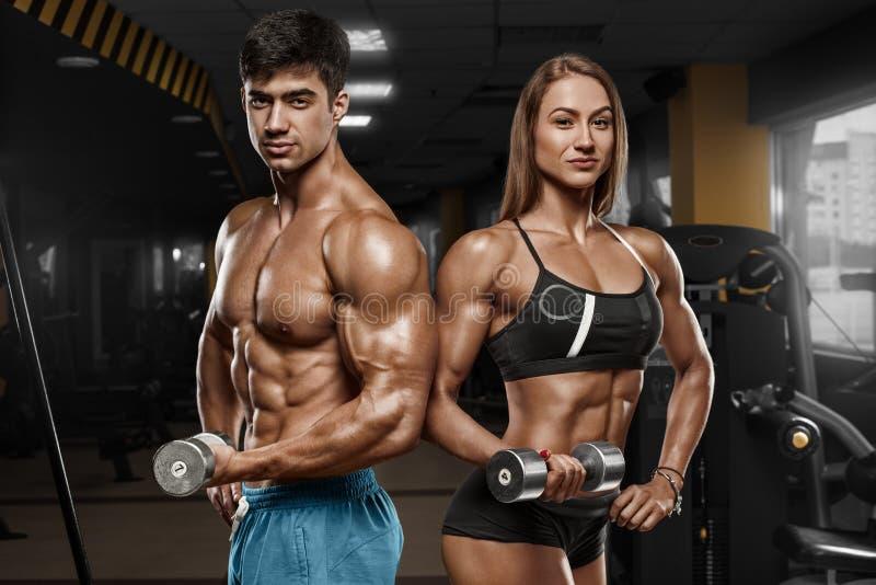 Φίλαθλο προκλητικό ζεύγος που παρουσιάζει μυ και workout στη γυμναστική Μυϊκό άτομο και wowan στοκ φωτογραφία