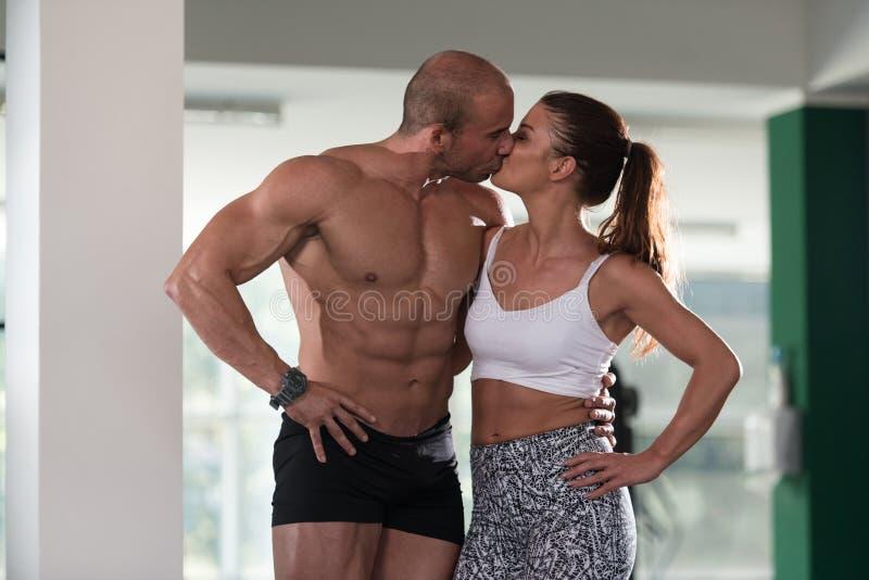 Φίλαθλο φίλημα ζεύγους σε μια γυμναστική στοκ εικόνες
