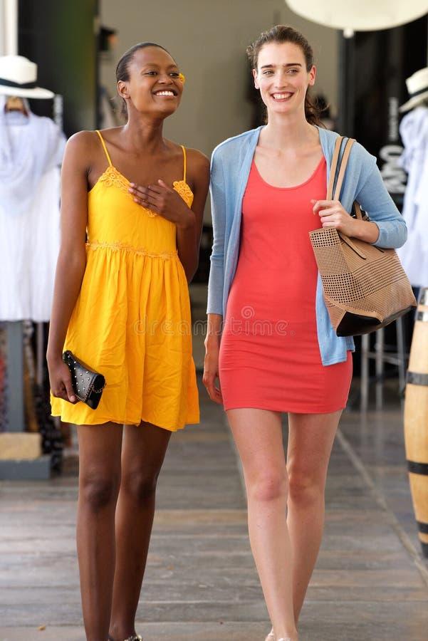 Φίλες που περπατούν σε ένα χαμόγελο λεωφόρων αγορών στοκ φωτογραφίες με δικαίωμα ελεύθερης χρήσης