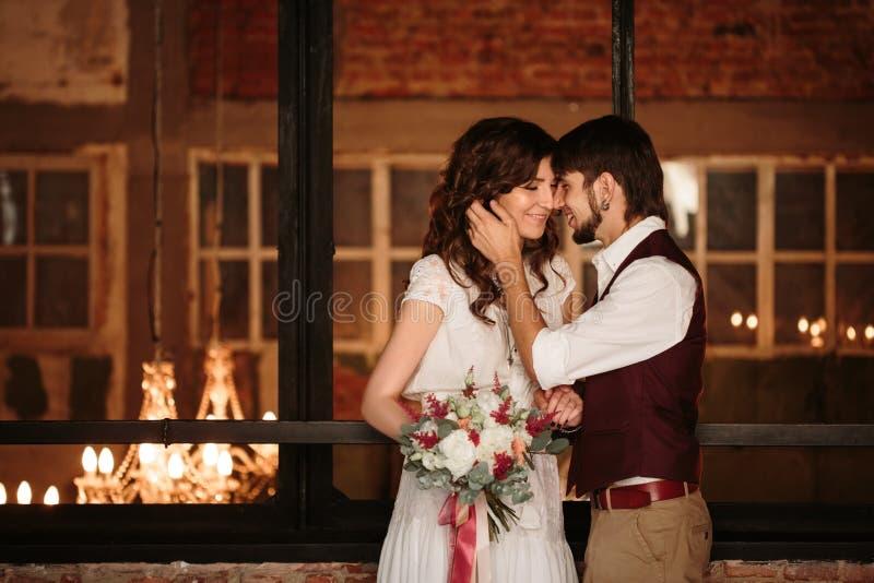 Φίλημα γαμήλιου ζεύγους στο εσωτερικό σοφιτών στοκ φωτογραφία