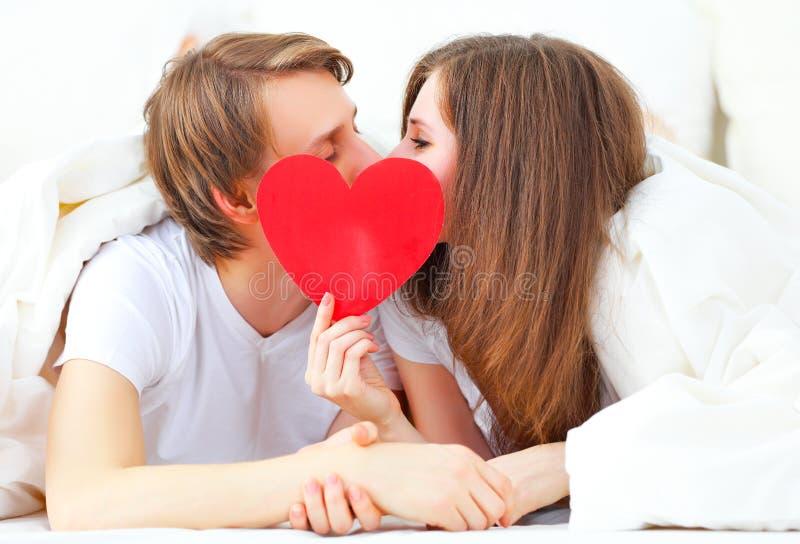 Φίλημα ζευγών εραστών με μια κόκκινη καρδιά στο κρεβάτι στοκ εικόνες με δικαίωμα ελεύθερης χρήσης