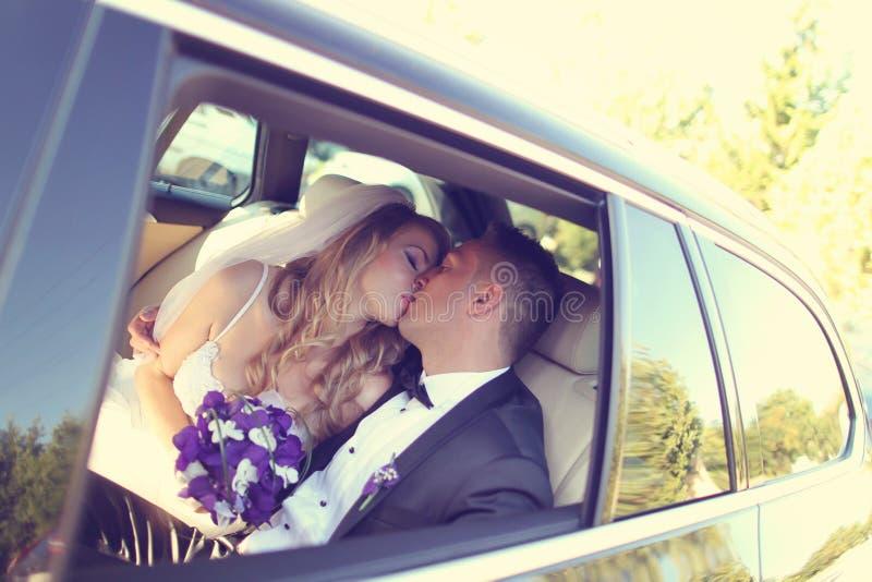 Φίλημα νεόνυμφων και νυφών στο αυτοκίνητο στοκ εικόνες