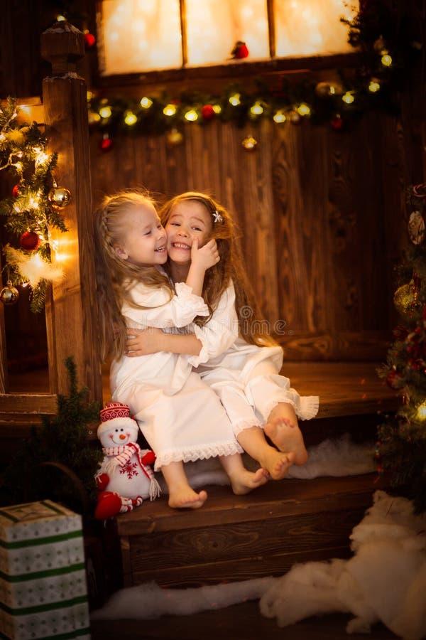 Φίλοι αδελφών κοριτσιών που αγκαλιάζουν τη συνεδρίαση στο χριστουγεννιάτικο δέντρο, έννοια στοκ εικόνες