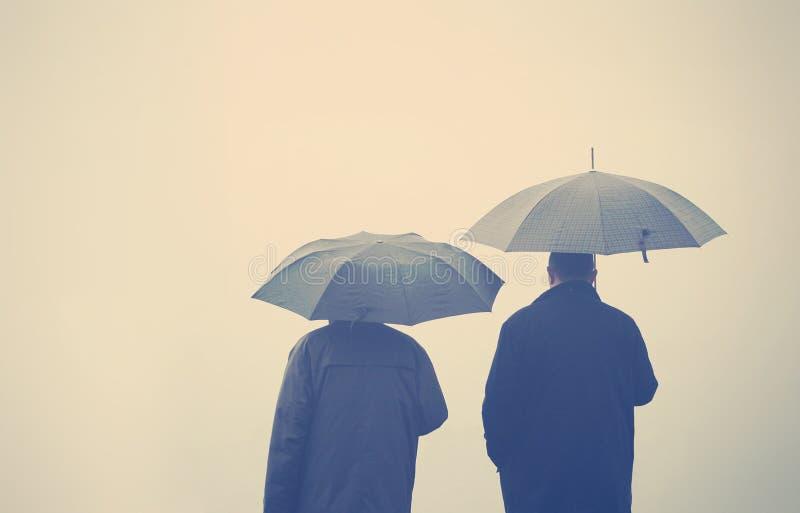 Φίλοι κάτω από ομπρέλες στοκ φωτογραφίες