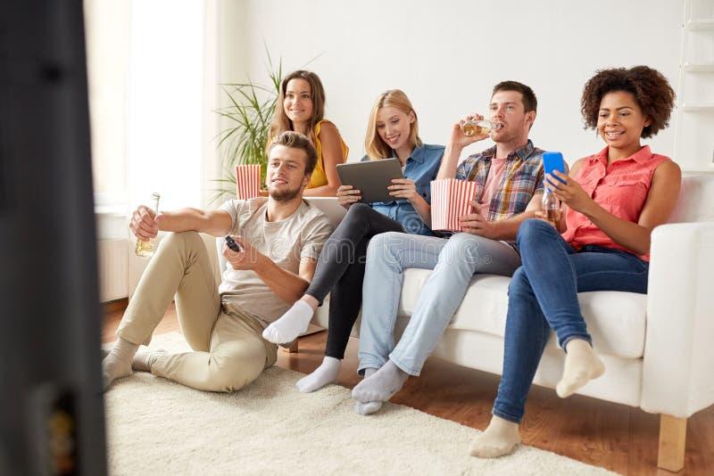 Φίλοι με τις συσκευές και μπύρα που προσέχει τη TV στο σπίτι στοκ φωτογραφία