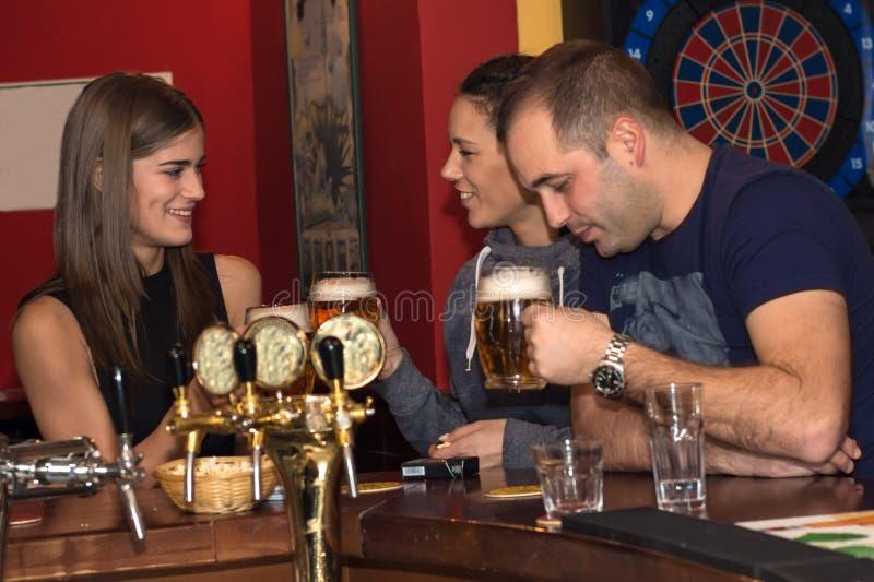 Φίλοι που έχουν τα ποτά σε έναν φραγμό στοκ εικόνα