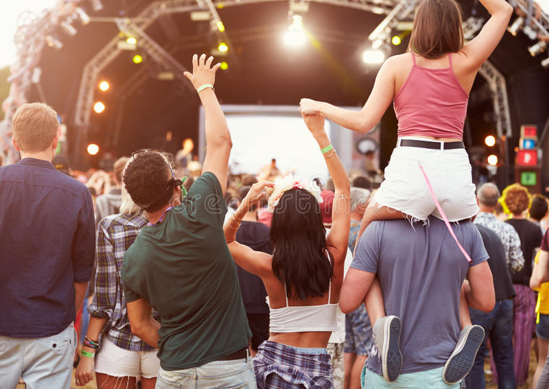 Φίλοι που έχουν τη διασκέδαση στο πλήθος στο φεστιβάλ μουσικής, πίσω άποψη στοκ εικόνες