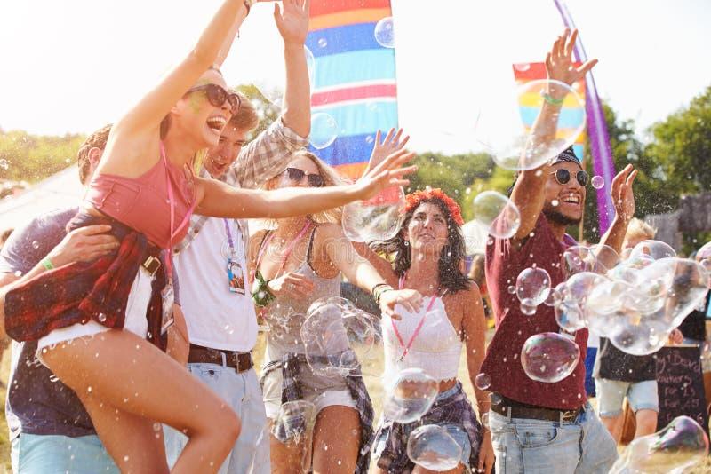 Φίλοι που απολαμβάνουν μια απόδοση σε ένα φεστιβάλ μουσικής στοκ εικόνες