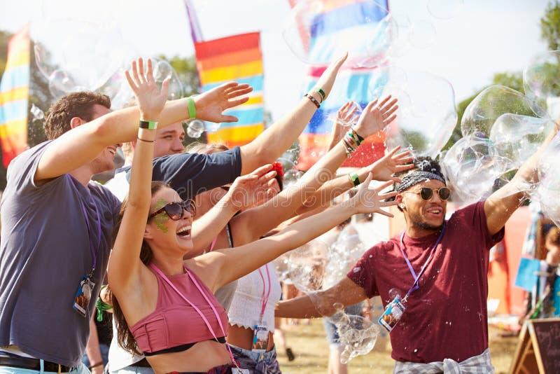 Φίλοι που απολαμβάνουν μια απόδοση σε ένα φεστιβάλ μουσικής στοκ φωτογραφία