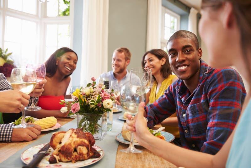Φίλοι που κάθονται στο σπίτι τον πίνακα για το κόμμα γευμάτων στοκ φωτογραφίες με δικαίωμα ελεύθερης χρήσης