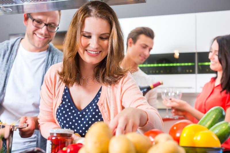 Φίλοι που μαγειρεύουν τα ζυμαρικά και το κρέας στην κουζίνα στοκ εικόνες