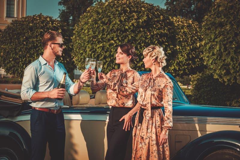 Φίλοι που πίνουν τη σαμπάνια κοντά στο κλασικό αυτοκίνητο στοκ εικόνα με δικαίωμα ελεύθερης χρήσης