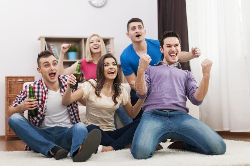 Φίλοι που προσέχουν το αθλητικό παιχνίδι TV στοκ φωτογραφίες