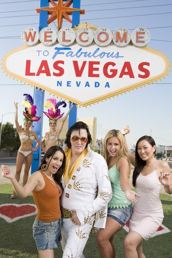 Φίλοι που στέκονται με το μιμητή του Elvis Presley και τους χορευτές χαρτοπαικτικών λεσχών στο υπόβαθρο στοκ φωτογραφίες