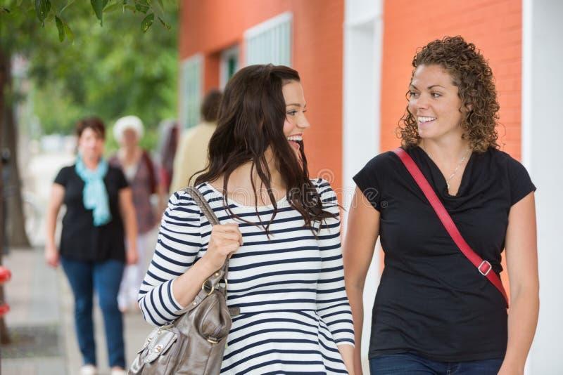 Φίλοι που συζητούν περπατώντας στο πεζοδρόμιο στοκ φωτογραφία με δικαίωμα ελεύθερης χρήσης