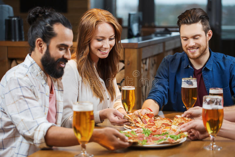 Φίλοι που τρώνε την πίτσα με την μπύρα στο εστιατόριο στοκ φωτογραφία με δικαίωμα ελεύθερης χρήσης