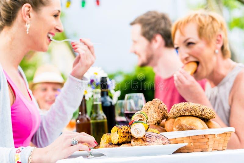 Φίλοι που τρώνε bbq το λουκάνικο και το κρέας στοκ εικόνες