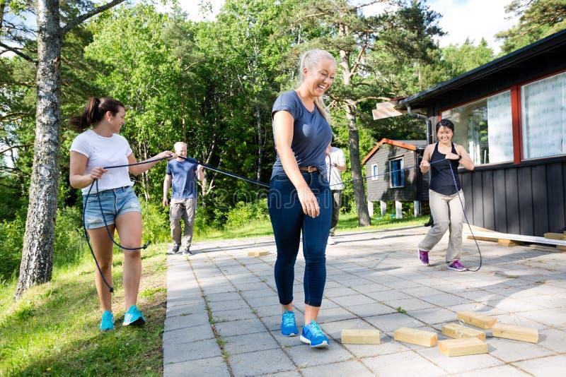 Φίλοι που φέρνουν τα σχοινιά περπατώντας προς τους ξύλινους φραγμούς στο PA στοκ εικόνες
