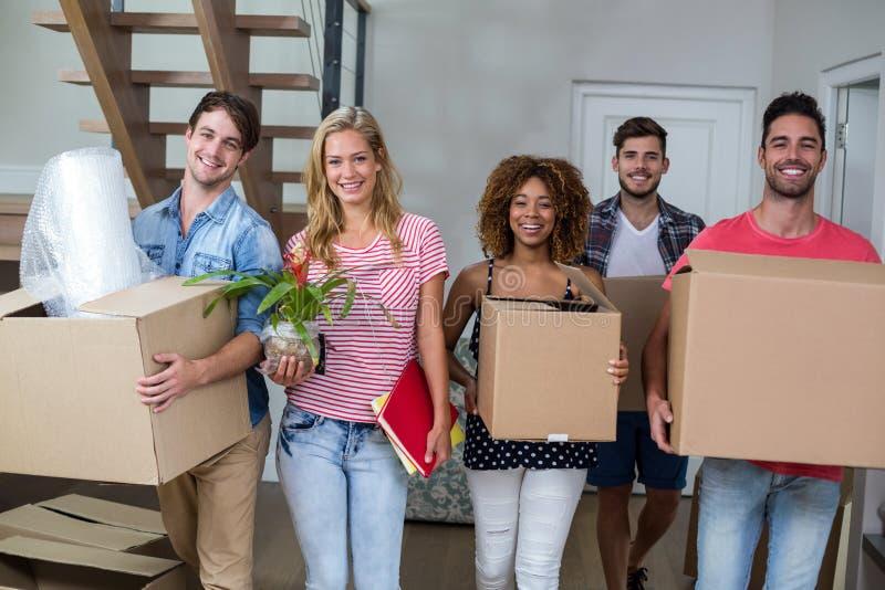 Φίλοι που χαμογελούν φέρνοντας το χαρτοκιβώτιο στο καινούργιο σπίτι στοκ εικόνες με δικαίωμα ελεύθερης χρήσης