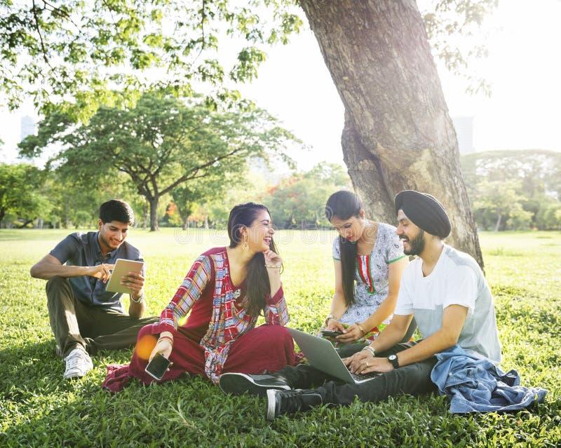 Φίλοι που χαλαρώνουν την έννοια συσκευών πάρκων συνεδρίασης στοκ εικόνες