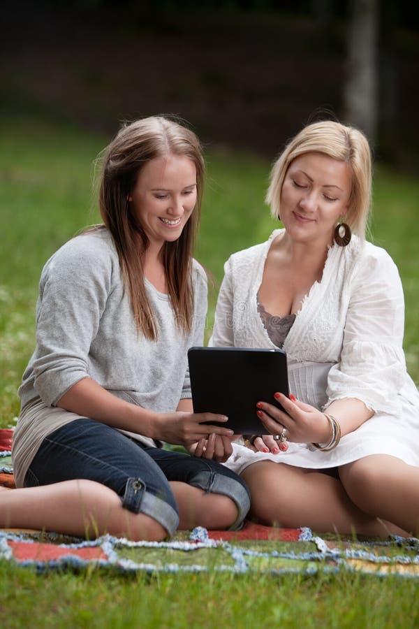 Φίλοι που χρησιμοποιούν την ψηφιακή ταμπλέτα στο πάρκο στοκ φωτογραφίες