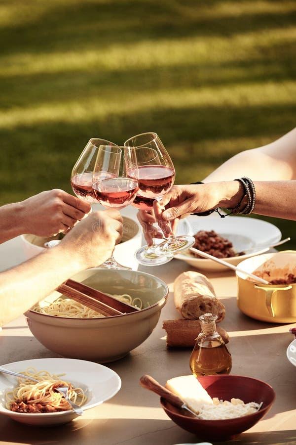 Φίλοι που ψήνουν με το κρασί πέρα από ένα γεύμα μακαρονιών στοκ φωτογραφία