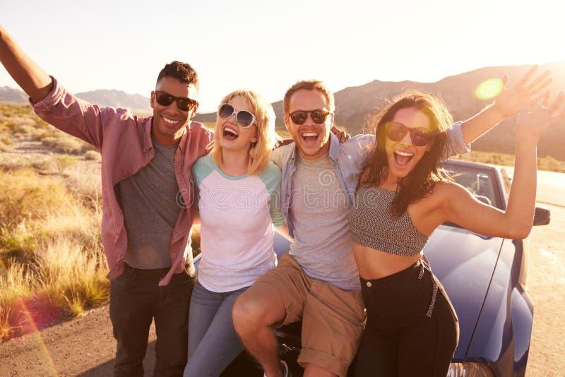 Φίλοι στη συνεδρίαση οδικού ταξιδιού στην κουκούλα του μετατρέψιμου αυτοκινήτου στοκ εικόνες με δικαίωμα ελεύθερης χρήσης