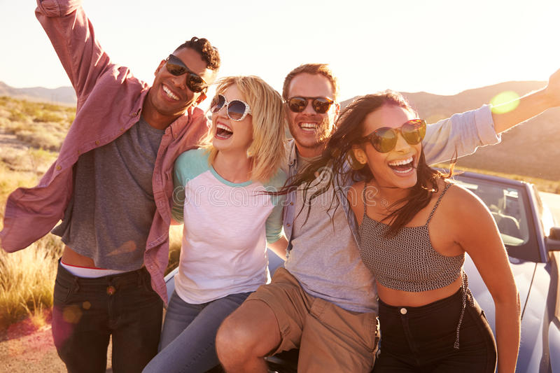 Φίλοι στη συνεδρίαση οδικού ταξιδιού στην κουκούλα του μετατρέψιμου αυτοκινήτου στοκ φωτογραφία με δικαίωμα ελεύθερης χρήσης