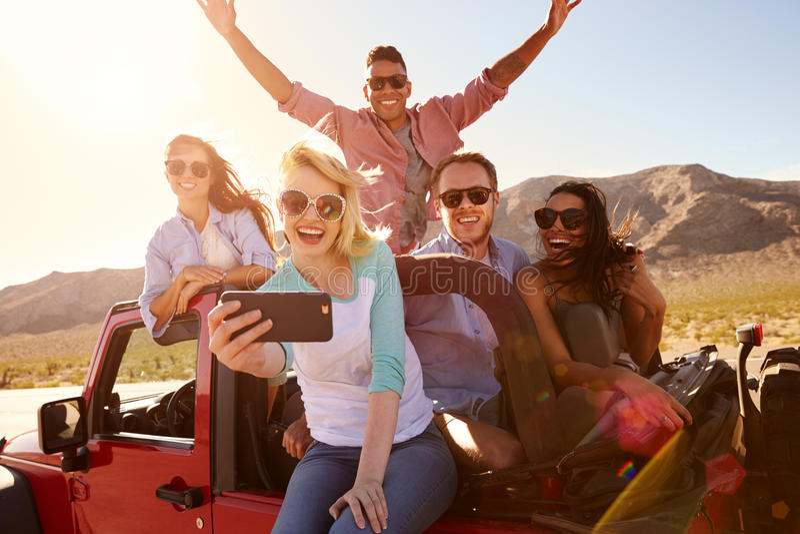 Φίλοι στο οδικό ταξίδι στο μετατρέψιμο αυτοκίνητο που παίρνει Selfie στοκ φωτογραφίες με δικαίωμα ελεύθερης χρήσης