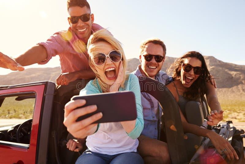 Φίλοι στο οδικό ταξίδι στο μετατρέψιμο αυτοκίνητο που παίρνει Selfie στοκ φωτογραφία