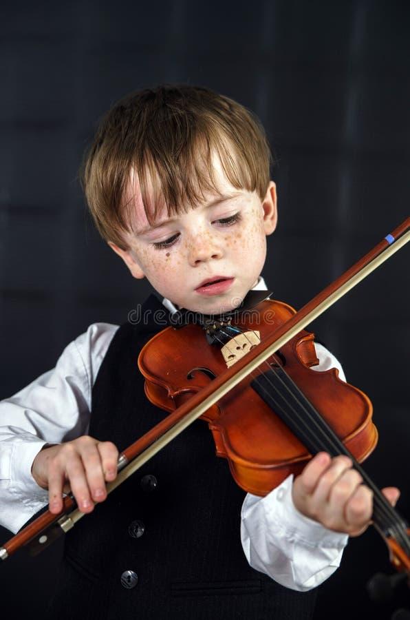 Φακιδοπρόσωπο βιολί παιχνιδιού αγοριών κόκκινος-τρίχας. στοκ εικόνα