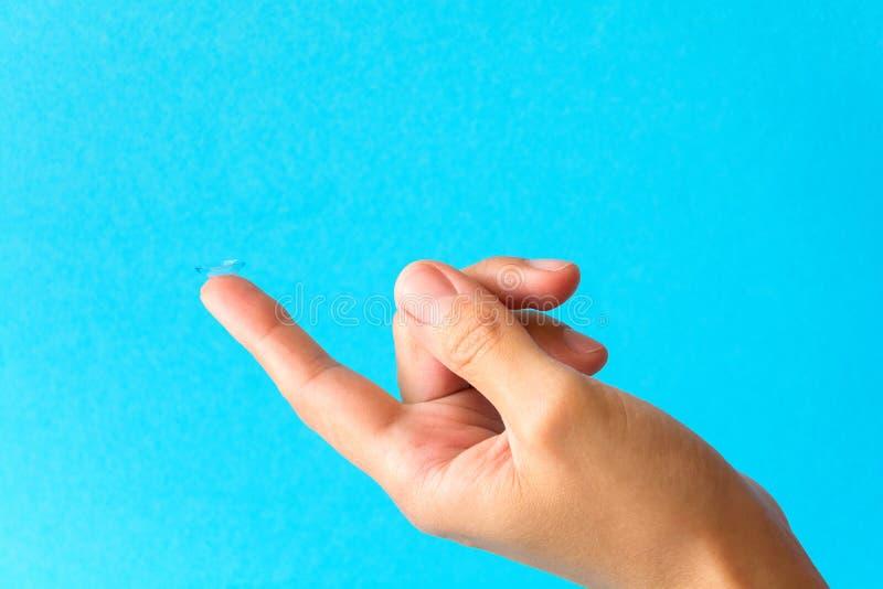 φακός επαφής στο δάχτυλο στο μπλε υπόβαθρο στοκ εικόνα με δικαίωμα ελεύθερης χρήσης
