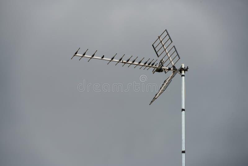 Φακός Telephoto μιας τηλεοπτικής κεραίας σε μια στέγη με ένα γκρίζο υπόβαθρο ουρανού στοκ εικόνες με δικαίωμα ελεύθερης χρήσης