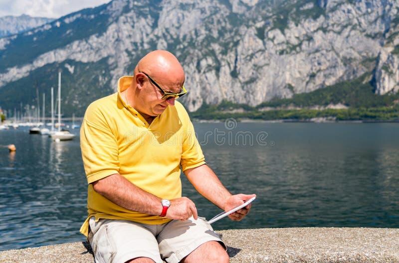 Φαλακρό άτομο με τη συνεδρίαση smartphone στην ακτή της λίμνης Como στην Ιταλία στοκ φωτογραφία με δικαίωμα ελεύθερης χρήσης