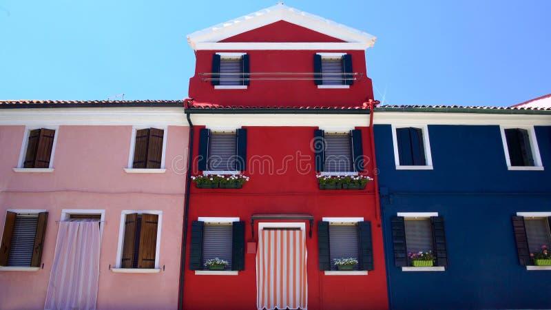 Φανταστικά ρόδινα, κόκκινα και μπλε σπίτια που διακοσμούνται με τα συμπαθητικά λουλούδια, νησί Burano στοκ εικόνα με δικαίωμα ελεύθερης χρήσης