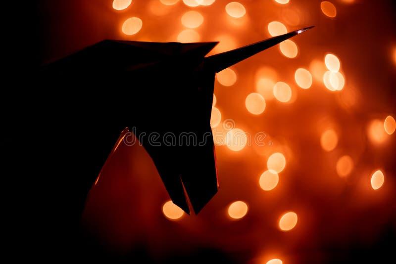 Φανταστική φωτογραφία της σκιαγραφίας ενός μονοκέρου στο υπόβαθρο ενός bokeh από τα φω'τα στοκ εικόνες