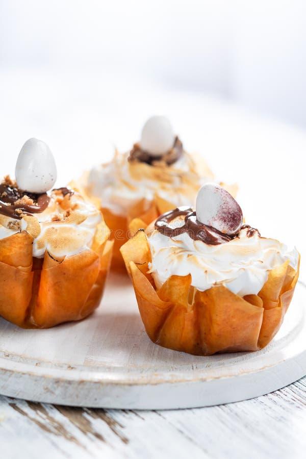 Φανταχτερά φλυτζάνια ζύμης Phyllo με τη μαρέγκα και τη λειωμένη σοκολάτα κοντά επάνω σε ένα πιάτο Άσπρο αγροτικό υπόβαθρο με το δ στοκ εικόνες