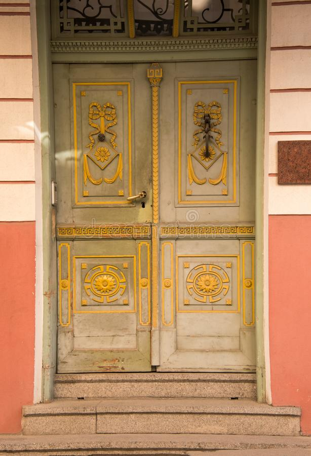 Φανταχτερές παλαιές πράσινες ξύλινες πόρτες με το κίτρινο σχέδιο Τρία βήματα πετρών που καταλήγουν στην πόρτα στοκ εικόνες