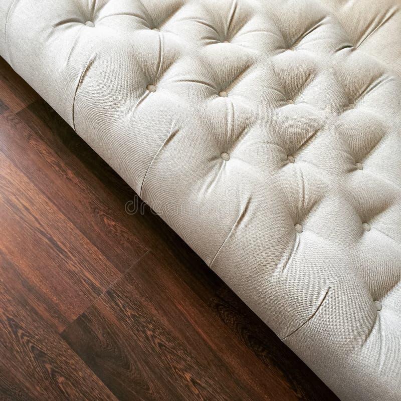 Φανταχτερός λευκός Οθωμανός στο σκοτεινό ξύλινο πάτωμα στοκ φωτογραφίες