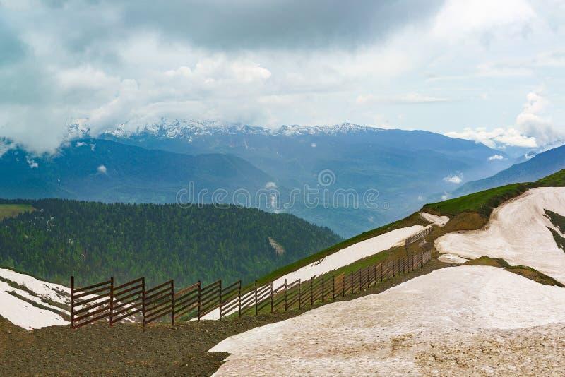 Φαράγγι βουνών και η κορυφή με τα υπόλοιπα του χιονιού το καλοκαίρι σύννεφων μια νεφελώδη ημέρα στοκ φωτογραφία με δικαίωμα ελεύθερης χρήσης
