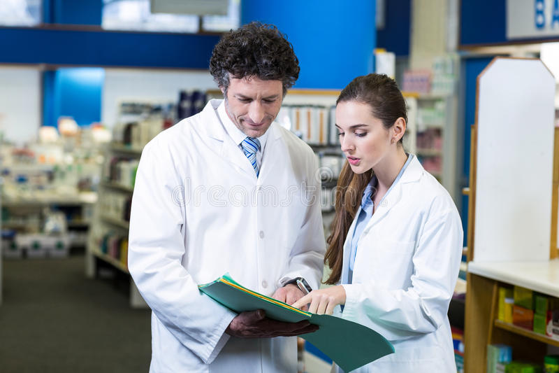 Φαρμακοποιοί που συζητούν πέρα από την ιατρική έκθεση στοκ εικόνες
